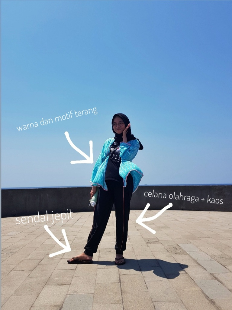 Woman wearing light blue cardigan, black outfit, and sandals in front of sea and sky