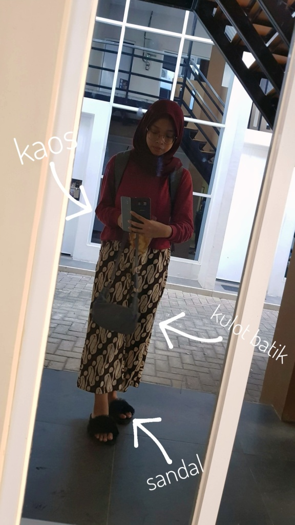 Woman taking self-photograph in front of a mirror showcasing her outfit