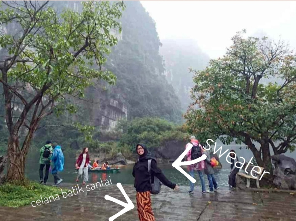 Woman posing in front of a river, trees, a mountain, and people.